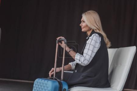woman with suitcase in waiting room