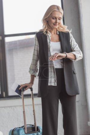Photo pour Femme souriante avec bagages et billet d'avion en regardant la montre - image libre de droit
