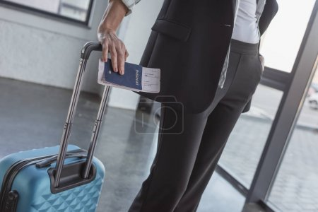 Photo for Cropped shot of woman with luggage and flight ticket in waiting room - Royalty Free Image