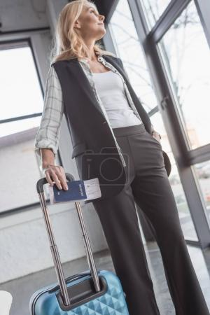 woman with luggage and flight ticket
