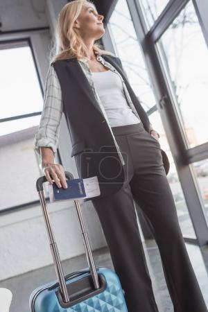 Photo pour Vue de dessous de femme avec bagages et vol billet dans la salle d'attente - image libre de droit