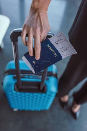Photo pour Recadrée tir de femme avec valise et vol billet dans la main - image libre de droit