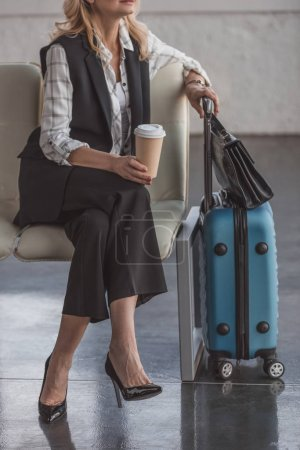 Photo for Cropped shot of woman with suitcase and coffee waiting for flight - Royalty Free Image
