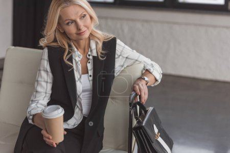 Photo for Thoughtful mature woman with suitcase and coffee waiting for flight - Royalty Free Image