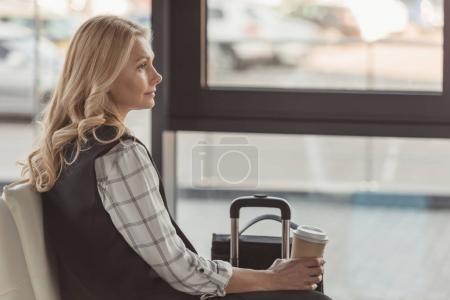 Photo pour Femme attrayante avec valise et café en attente de vol - image libre de droit