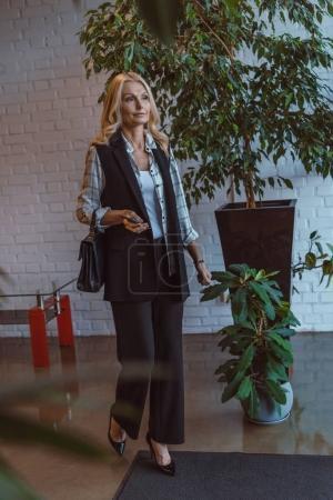 Photo pour Mature femme élégante dans le hall de bureau style loft - image libre de droit