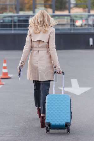 woman in trench coat walking with luggage