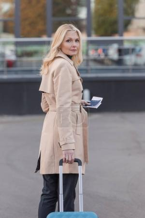 woman in trench coat with flight ticket