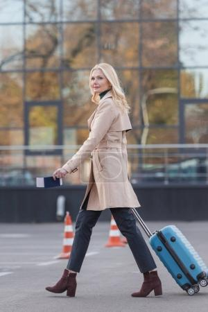 woman with suitcase and flight ticket