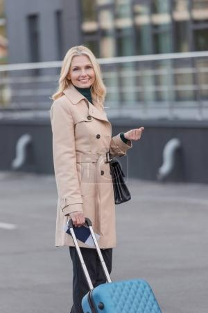 woman in trench coat with luggage