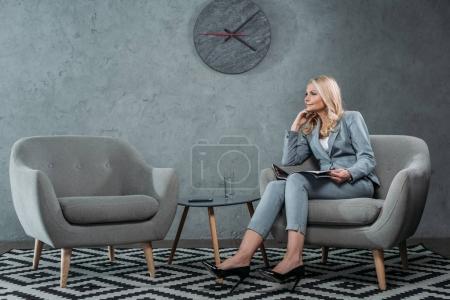 Photo pour Femme d'affaires assis dans le fauteuil avec le magazine à Hall de bureau - image libre de droit