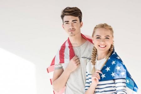 Photo pour Beau jeune couple tenant drapeau américain et souriant à la caméra sur gris - image libre de droit