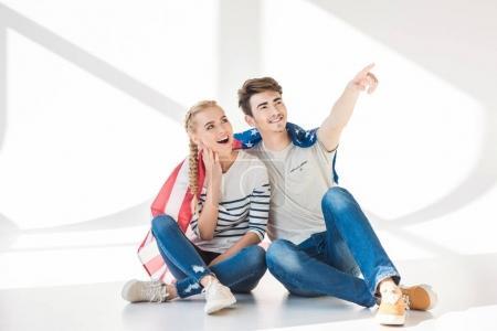 Photo pour Joyeux jeune couple avec drapeau américain assis ensemble et regardant loin sur gris - image libre de droit