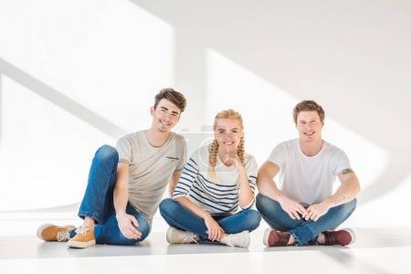 Foto de Felizes jóvenes amigos sentados juntos y sonriendo a cámara en gris - Imagen libre de derechos