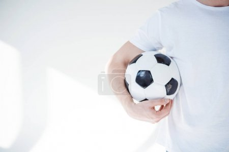 Photo for Cropped shot of young man holding soccer ball on grey - Royalty Free Image
