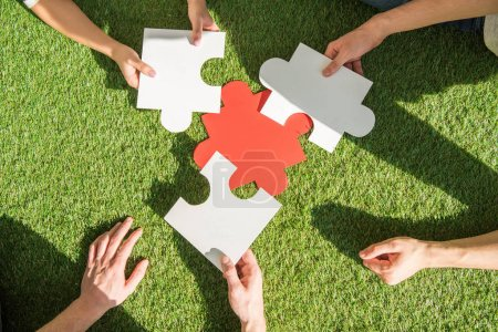 Photo for Close-up partial view of hands holding puzzle pieces above green grass - Royalty Free Image