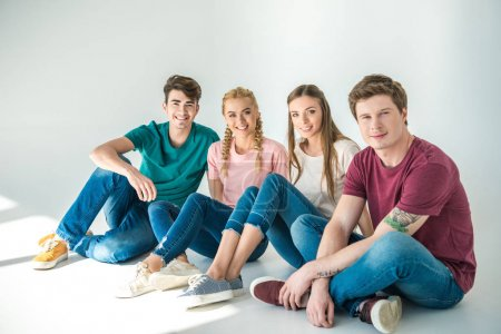 Photo for Happy young friends sitting together and smiling at camera on grey - Royalty Free Image