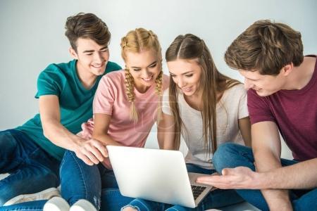 Foto de Amigos jóvenes felices usando laptop sentado juntos en gris - Imagen libre de derechos