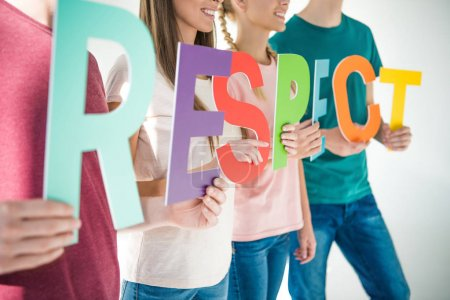Photo for Cropped shot of young friends holding word respect on grey - Royalty Free Image