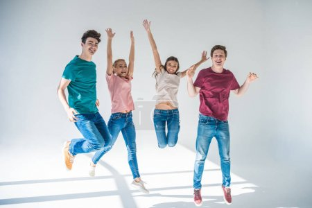 Photo for Happy young people jumping together and smiling at camera on grey - Royalty Free Image