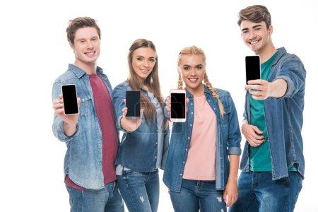 Foto de Sonrientes joven amigos con teléfonos inteligentes con pantallas en blanco aislados en blanco - Imagen libre de derechos