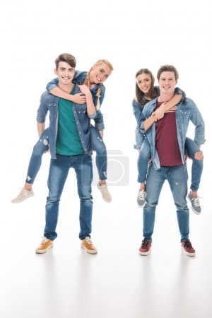 happy young friends piggybacking