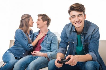 Photo pour Jeune homme jouant avec la manette de jeu alors que le jeune couple caresses derrière isolé sur blanc souriant - image libre de droit