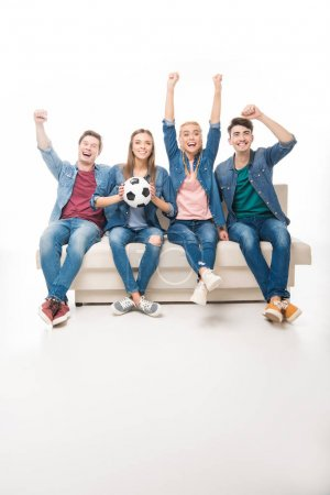 friends with soccer ball sitting on sofa