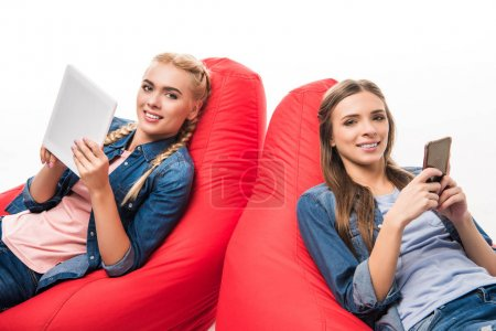 Photo for Beautiful young women using digital devices while sitting in bean bag chairs and smiling at camera isolated on white - Royalty Free Image