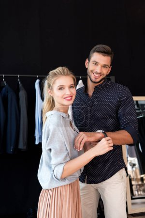 Photo for Beautiful young couple smiling at camera while buying male wristwatch in boutique - Royalty Free Image