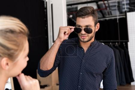Man wearing sunglasses in boutique
