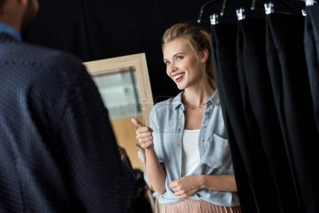 Couple choosing male clothes in boutique