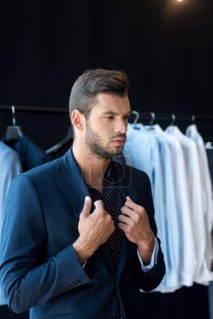 Photo pour Beau jeune homme d'affaires essayant costume et détournant les yeux en boutique - image libre de droit