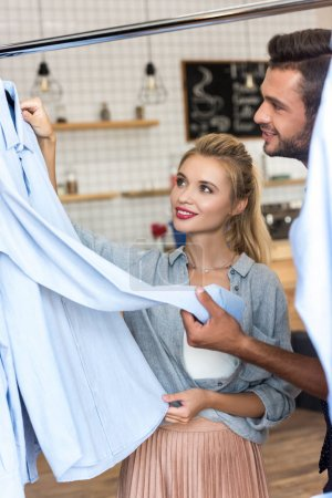 Foto de Sonriente joven pareja elegir camisas elegante de boutique - Imagen libre de derechos