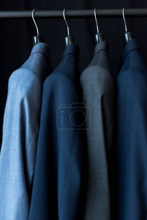 Photo for Fashionable male suit jackets on hangers in boutique - Royalty Free Image