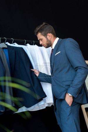 Photo pour Side view of handsome young businessman choosing suit in boutique - image libre de droit