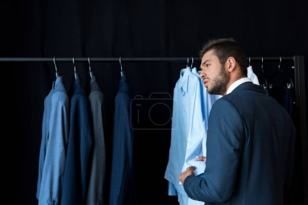 businessman choosing suit in boutique