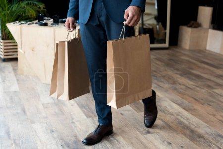 Photo pour Recadrée tir du jeune homme d'affaires, portant des sacs de shopping dans la boutique - image libre de droit