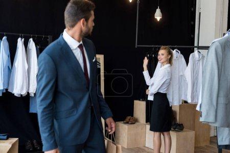 Photo pour Jeune homme d'affaires regardant jeune femme agitant la main dans la boutique - image libre de droit