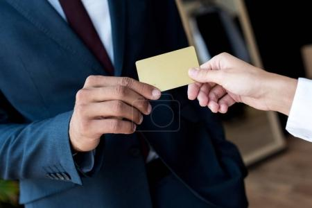 Photo for Close-up partial view of businessman and seller holding blank card in boutique - Royalty Free Image