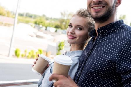 young couple with coffee to go