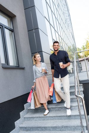 Photo for Smiling young couple with paper bags and coffee to go walking together outside - Royalty Free Image