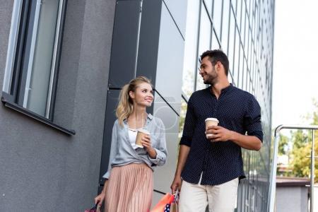 Foto de Jóvenes felices pareja con vasos de papel y bolsas de compras, caminar juntos en la calle - Imagen libre de derechos