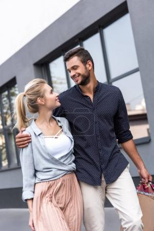 Photo for Happy young couple smiling each other while walking with shopping bags on street - Royalty Free Image