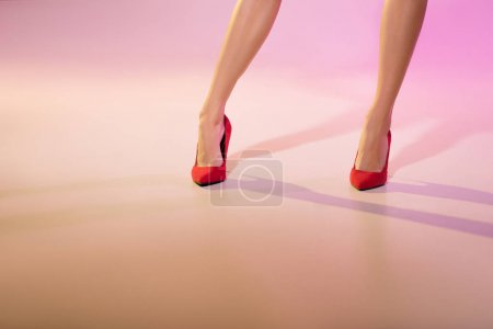Photo for Low section of woman legs in red heels, on pink - Royalty Free Image