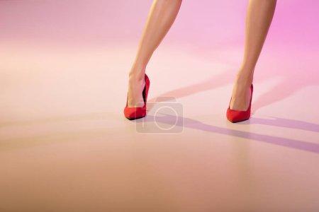 Photo pour Section basses de jambes de femme en talons rouges, rose - image libre de droit