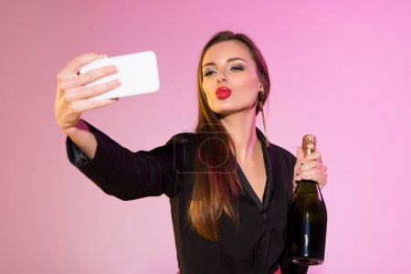 woman with champagne taking selfie