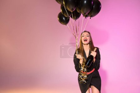 Photo for Excited beautiful woman with champagne bottle and black balloons - Royalty Free Image