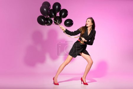 Photo for Stylish attractive woman holding black balloons, on pink - Royalty Free Image