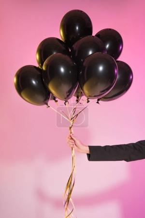 Photo pour Vue recadrée de la femme tenant des ballons noirs, sur rose - image libre de droit